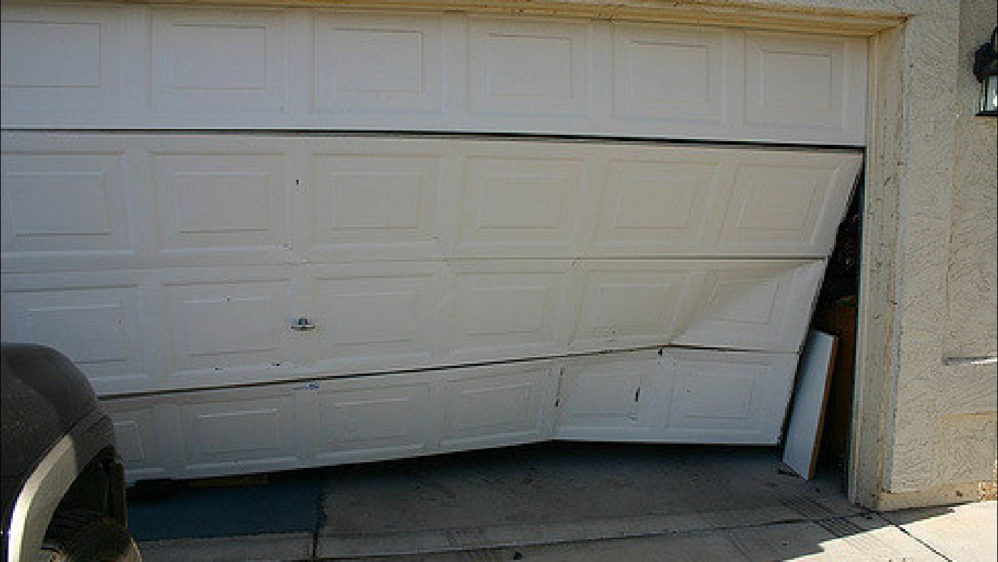 Garage security tips for garage doors windows openers toronto image of an overhead roll up garage door pushed in by a car gaining access rubansaba